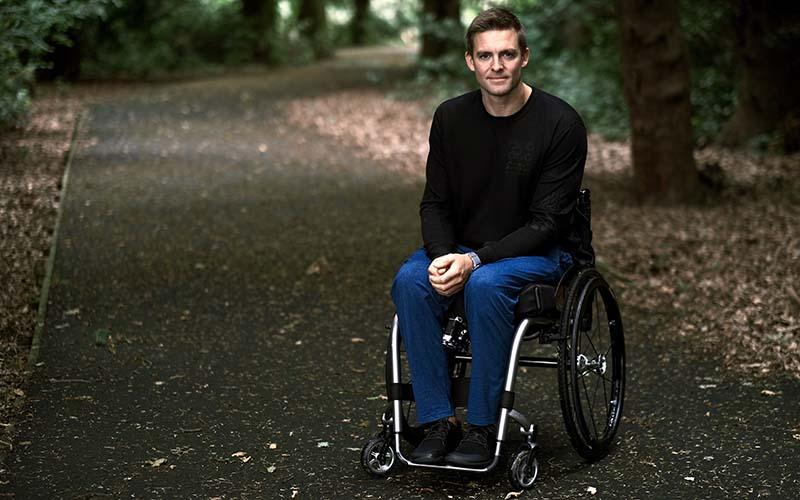 Man in wheelchair on woodland path