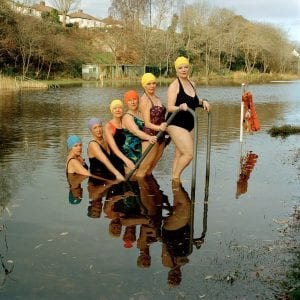 Synchonised swimmers stepping out of lake