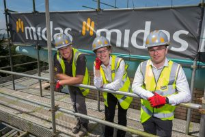 Three trainees in hi-visibility jackets on a Midas building site.