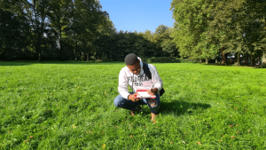 Black, male student crouches to take notes in a field