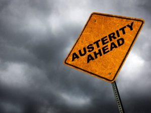 An orange sign against a grey sky reading Austerity Ahead