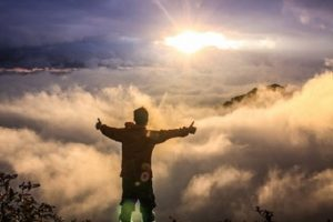A photo of a man on top of a mountain above the clouds staring into the sun