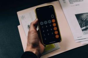 iPhone calculator open over paperwork