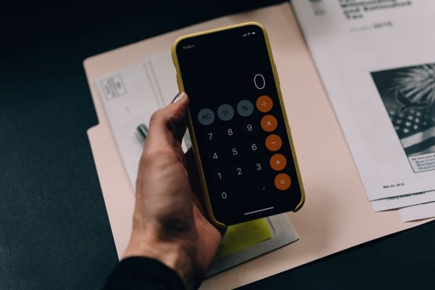iPhone calculator open over paperwork
